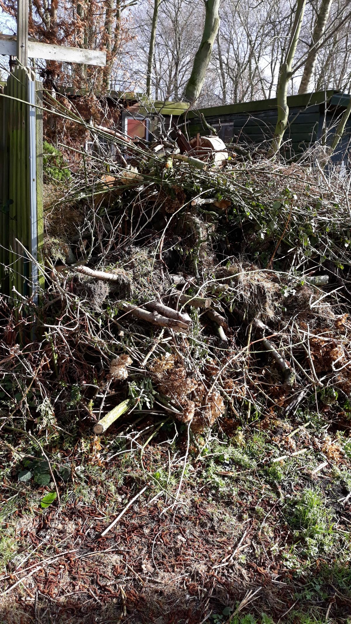 De stapel hout- en snoeiafval groeit uit deklauwen